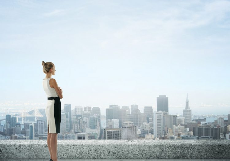 businesswoman on roof looking at city